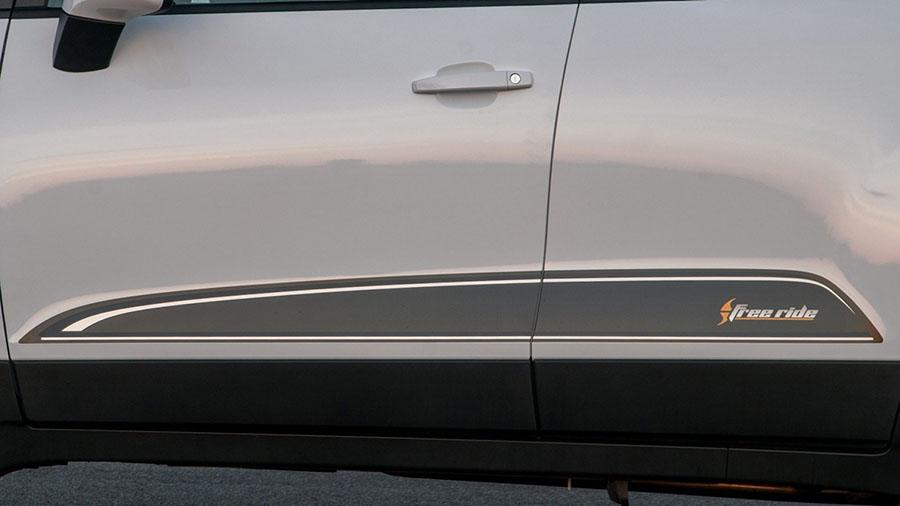 O visual da Freeride na lateral vem com adesivos, adesivo preto fosco na coluna B, maçanetas e retrovisores pintados na cor do veículo.